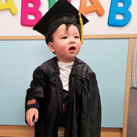 Child at preschool dressed in graduation gown