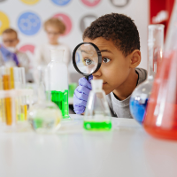 Child in science class holding magnifying glass to eye