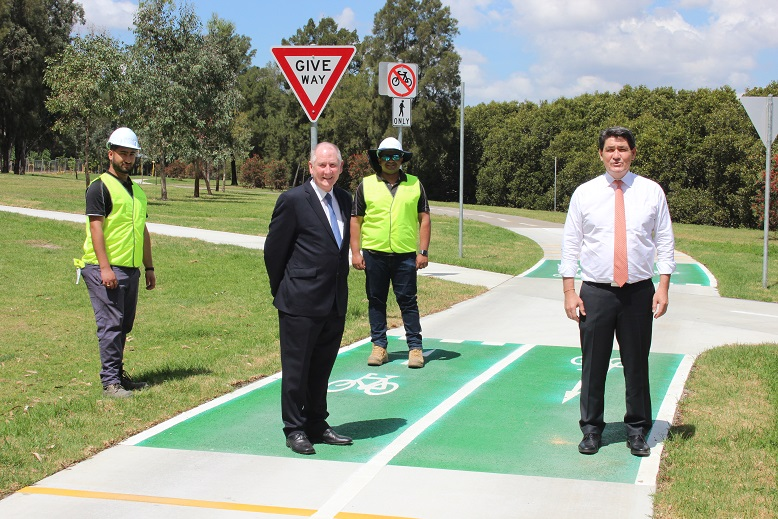 City of Parramatta Lord Mayor Cr Bob Dwyer at the new Eastern Foreshore separated cycleway with Acting Minister for Sport, the Honourable Geoff Lee MP (right), contactor for Devcon Civil Pty Ltd, Birat Tiwari (left), and contactor for Devcon Civil Pty Ltd, Phinu Mathew (back).
