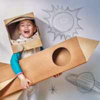 Child dressed as an astronaut holding a cardboard rocket