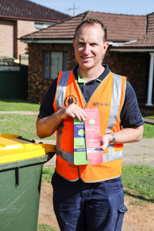 Council recycling inspector holding red and green tags