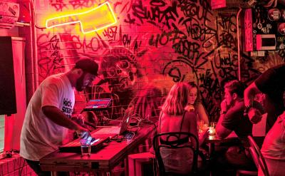 Image of people dining out. A DJ is in frame playing music, whilst patrons are dining.