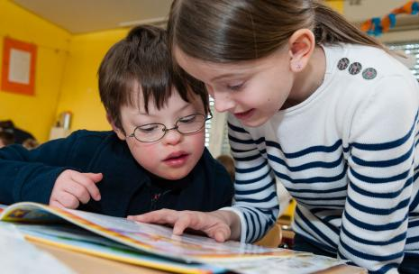 : Image of a boy and girl reading a book in an inclusive education setting