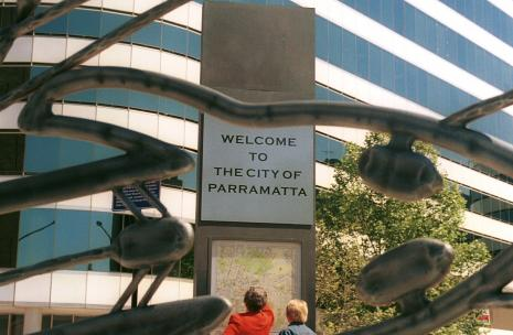 Welcome to the City of Parramatta with metal art in front with two people looking at a map