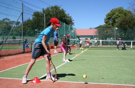 Young person in red cap playing tennis with other children