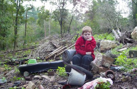 Child sitting in a heap of rubbish